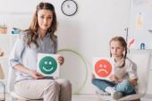 psicologo adulto e bambino che tiene emozioni felici e tristi facce carte