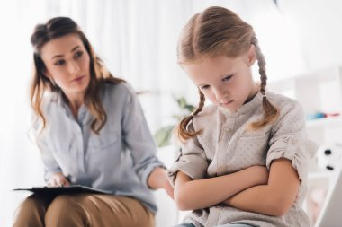 adult psychologist talking to depressed child with crossed arms