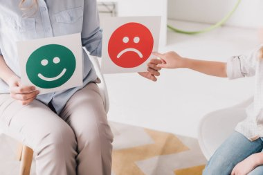Cropped shot of psychologist showing happy and sad emotion faces cards to child stock vector