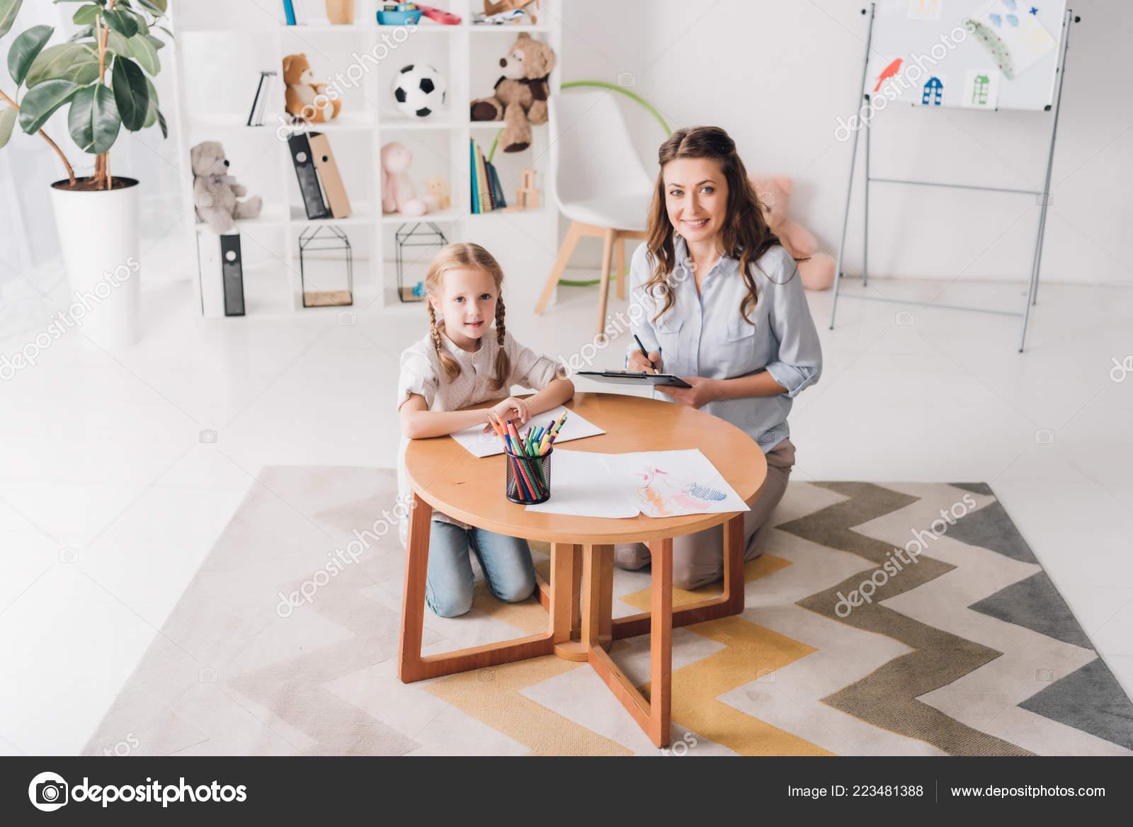 45b2f53d7 Psicólogo feliz con portapapeles sentarse cerca del niño mientras ella  dibujaba con lápices de colores y mirando a cámara — Foto de ...