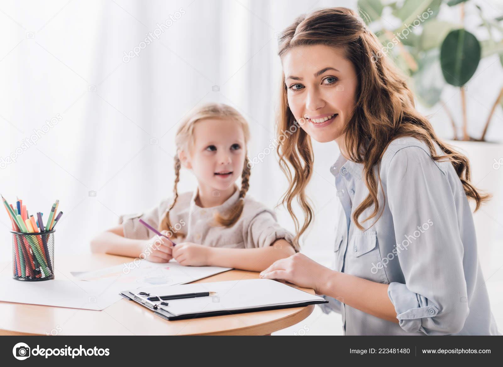 3c0d7c8ba Psicólogo sonriente con portapapeles sentarse cerca del niño mientras ella  dibujaba con lápices de colores y mirando a cámara — Foto de ...