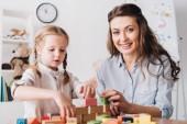 Fotografie glückliche Mutter und Kind, Blick in die Kamera während des Spielens mit Blöcken