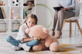 Fotografie sad little child with teddy bear sitting on floor with psychologist sitting on background