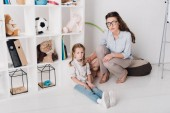 Fotografie female psychologist supporting depressed child while she sitting on floor and looking at camera