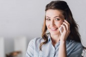 Photo close-up portrait of smiling adult woman talking by phone and looking at camera
