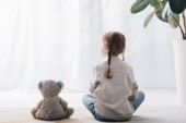 Photo rear view of little child sitting on floor with teddy bear and looking away