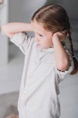 Fotografie depressed little child covering ears with hands