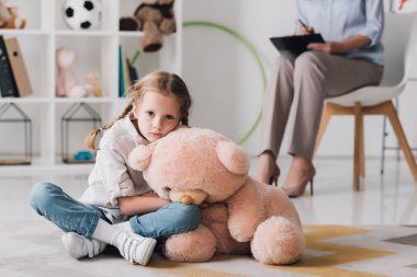 sad little child with teddy bear sitting on floor with psychologist sitting on background