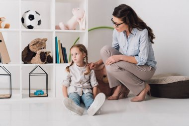 adult female psychologist supporting depressed child while she sitting on floor