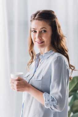 happy adult woman holding cup of warming beverage and looking at camera