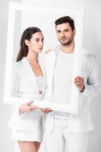 Photo adult couple in total white posing with frame