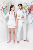 Photo fashion shoot of couple in total white drawing with paints on wall