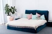 Vnitřní pohled ložnice s modrou postelí a hračky