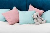 Medvídek položil na postel s polštáři na pozadí