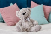 Fotografie Close up horizontal view of teddy bear sitting on the bed with pillows on background