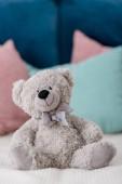 Vertikální pohled medvídek sedí na posteli s polštáři na pozadí na plochu