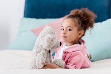 Cute african american child laying on the bed with her teddy bear stock vector