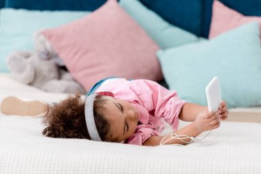 adorable african american child lying on the bed and listening music on her smartphone in headphones