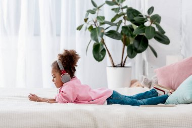 side view of cute african american child lying on the bed and listening music on her smartphone in headphones