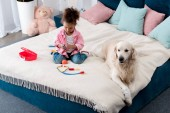 Photo Cute african american child playing with toys on the bed with white dog lying beside