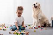 Roztomilý africké americké dítě hrát si s barevnými hračka kostky a šťastný pes