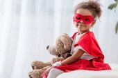 Fotografie Adorable little african american kid in superhero costume and mask with teddy bear