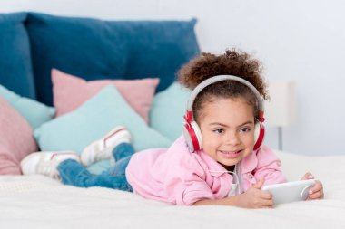 smiling african american kid lying on the bed and listening music in headphones