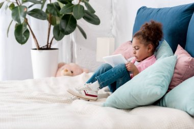 curly african american child sitting on the bed with digital tablet