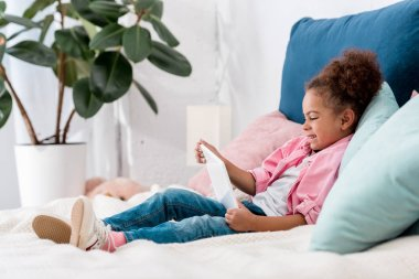 smilng african american kid lying on the bed with digital tablet