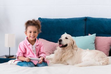 smiling african american kid sitting on the bed with smartphone and golden retriever