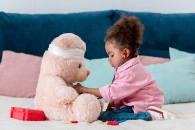 Little african american child in pink jacket playing the doctor  with teddy bear