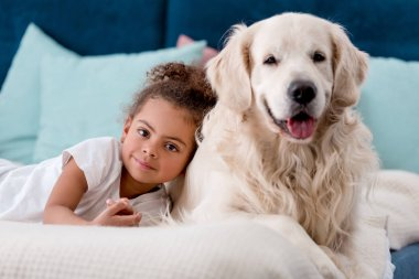 Adorable african american child with happy dog smiling at camera