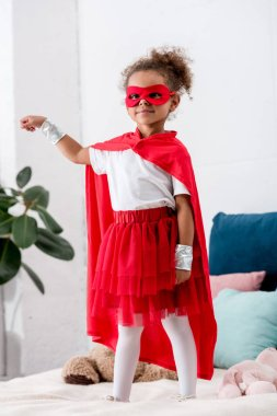 Cute little african american kid in red superhero costume gesturing while standing on bed