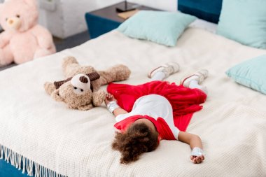 little child in red superhero costume with teddy bear lying on bed