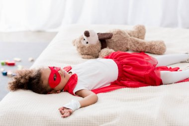 Cute little african american child in superhero costume and mask lying on bed with teddy bear