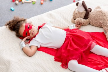 Adorable little african american child in superhero costume lying on bed with teddy bear