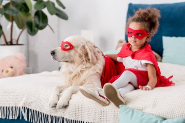 Adorable little african american kid with dog in superhero costumes sitting on bed