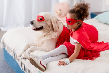 Adorable little african american kid with dog in red superhero costumes sitting on bed
