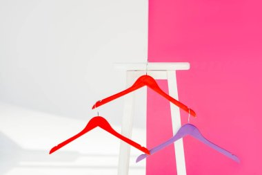 close up of multicolored painted hangers with white wooden chair