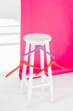 multicolored painted hangers with white wooden chair and pink wallaper