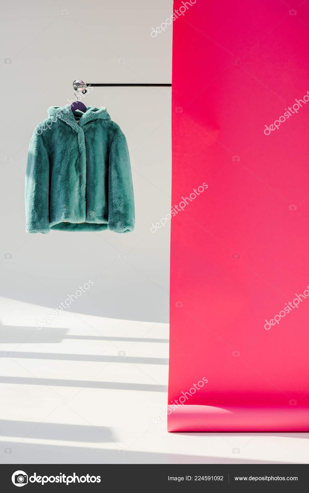 Nadýchané zelené umělé kožešiny kabát na věšák s růžové tapety– stock  obrázky 851b5346eed