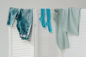 Fotografie close up of blue clothes hanging on white room divider isolated on grey