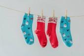 Nahaufnahme von bunten festlichen Wintersocken, die an der Wäscheleine hängen, mit Wäscheklammern, die auf grau isoliert sind