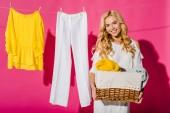 Fotografie zblízka krásné ženy držící proutěný koš s oblečením, které visí na prádelní šňůru