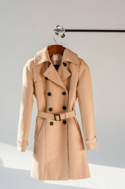 beige trench coat with belt and black buttons on hanger