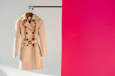 elegant beige trench coat on hanger at pink and grey background