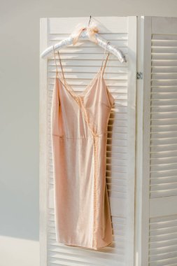 close up of silk nightie with lace hanging on white room divider