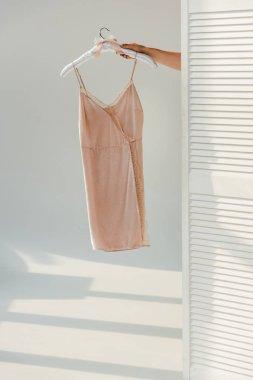 Female hand holding hanger with silk nightie stock vector