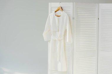 Elegant white dress hanging on wooden room divider stock vector