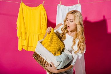 close up of emotional woman getting out clothes from wicker basket